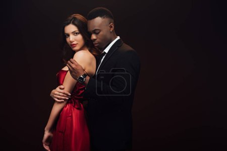 Photo for African american man undressing beautiful woman in red dress isolated on black with copy space - Royalty Free Image