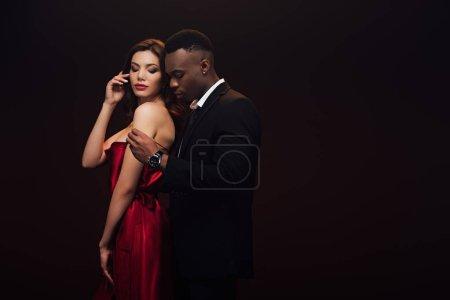 Photo pour Beau couple interracial sensuel en tenue formelle posant isolé sur noir avec espace de copie - image libre de droit