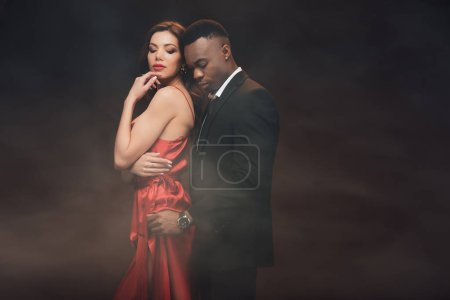 Photo for African american man embracing beautiful woman in red dress on dark with smoke - Royalty Free Image