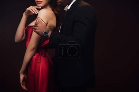 Photo for Partial view of african american man undressing woman in red dress isolated on black with copy space - Royalty Free Image