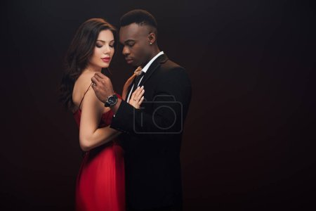 beautiful sensual interracial couple in formal wear embracing isolated on black with copy space