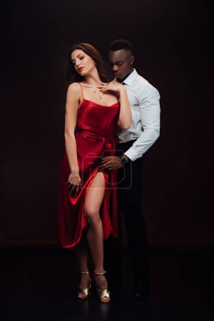Photo for Beautiful seductive interracial couple in formal wear posing isolated on black - Royalty Free Image