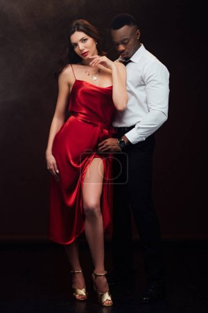 Photo for Beautiful sensual interracial couple in formal wear posing isolated on black - Royalty Free Image