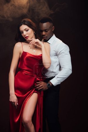 Photo for Beautiful sensual interracial couple in formal wear posing on black with smoke - Royalty Free Image