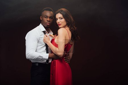 Photo for Beautiful woman in red dress looking at camera and undressing shirt of african american man isolated on black - Royalty Free Image