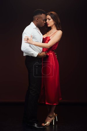 Photo for Handsome african american man embracing beautiful woman in red dress isolated on black - Royalty Free Image