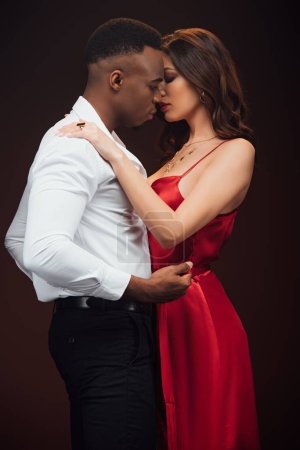 Photo for Sensual interracial couple in formal wear embracing isolated on black - Royalty Free Image