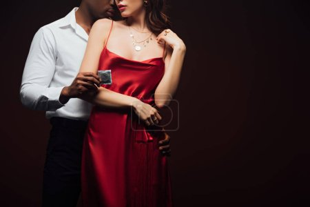 Photo for Cropped view of african american man holding condom and embracing woman in red dress isolated on black with copy space - Royalty Free Image