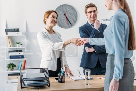 Photo for Cropped view of woman shaking hands with cheerful recruiter near handsome coworker in glasses - Royalty Free Image