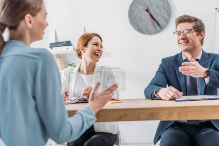 Photo for Cheerful recruiter looking at coworker in glasses gesturing while speaking with attractive applicant - Royalty Free Image