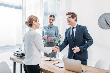 cheerful recruiter shaking hands with woman near colleague in office