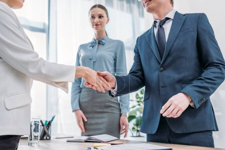 Photo for Cropped view of cheerful recruiter shaking hands with woman near attractive colleague in office - Royalty Free Image