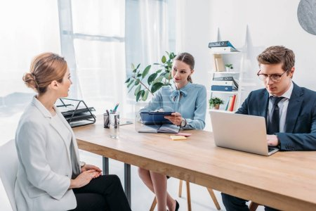 Photo for Woman talking with recruiter holding clipboard while coworker using laptop on job interview - Royalty Free Image