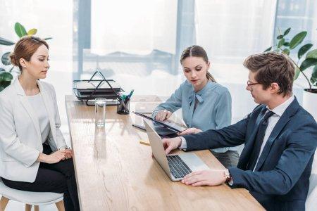 Photo pour Recruteur regardant l'ordinateur portatif près de collègue et les femmes sur l'entrevue d'emploi - image libre de droit