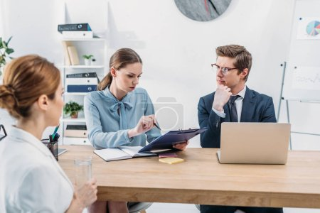 Photo for Attractive recruiter talking and looking at clipboard near coworker in glasses and employee - Royalty Free Image