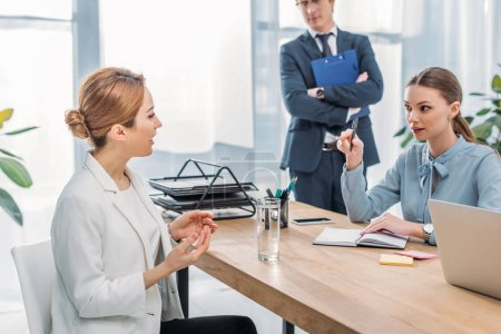 Photo pour Femme attirante parlant avec le recruteur près de collègue pendant l'entrevue d'emploi - image libre de droit