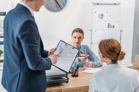 Photo pour Foyer sélectif du recruteur attrayant regardant la femme près de collègue retenant le presse-papiers avec le lettrage CV curriculum vitae - image libre de droit