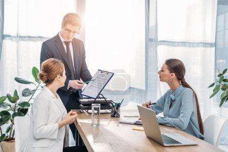 Photo pour Beau recruteur tenant le presse-papiers près de femme sur l'entrevue d'emploi - image libre de droit