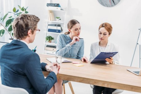 attractive recruiters looking at clipboard near man sitting with clenched hands