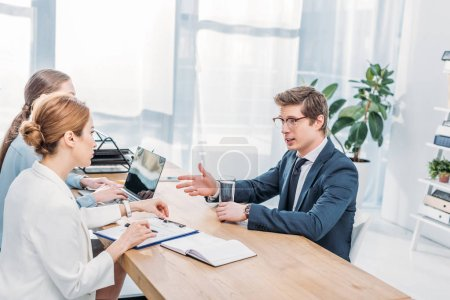 Photo for Handsome employee in glasses talking and gesturing on job interview - Royalty Free Image