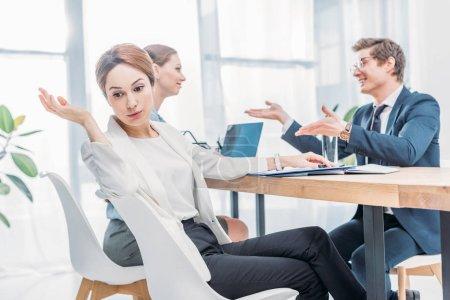 Photo pour Attrayant recruteur émotionnel gestes près de l'homme dans les verres parler pendant l'entretien d'embauche - image libre de droit