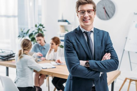 Photo for Selective focus of cheerful recruiter in glasses standing with crossed arms near coworkers - Royalty Free Image