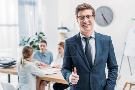 selective focus of cheerful recruiter in glasses showing thumb up near coworkers