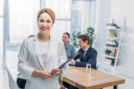 Photo for Selective focus of cheerful recruiter standing with clipboard near coworkers - Royalty Free Image