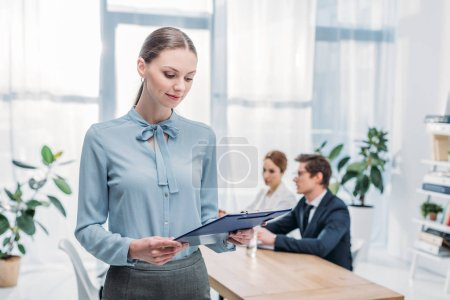 Photo for Selective focus of attractive recruiter looking at clipboard near colleagues - Royalty Free Image