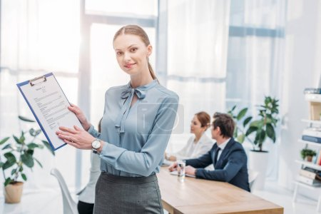 Photo for Selective focus of cheerful recruiter holding clipboard with resume cv lettering near coworkers - Royalty Free Image