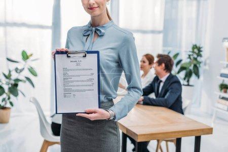 Photo pour Vue recadrée de joyeux recruteur tenant le presse-papiers avec CV curriculum vitae près des collègues - image libre de droit
