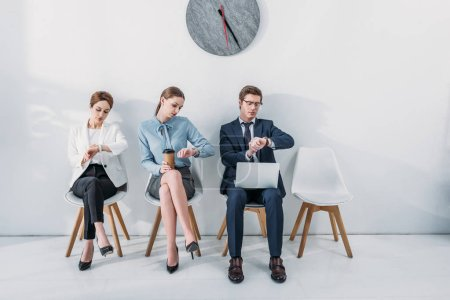 Photo for Women and man with laptop looking at watches while waiting job interview - Royalty Free Image