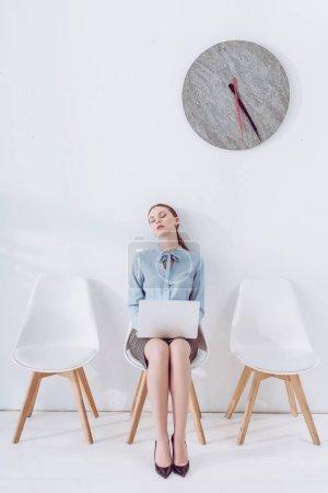 Photo pour Femme attirante avec l'ordinateur portatif dormant sur la chaise en attendant l'entrevue d'emploi - image libre de droit