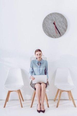 Photo pour Employé attrayant s'asseyant sur la chaise avec l'ordinateur portatif en attendant l'entrevue d'emploi - image libre de droit