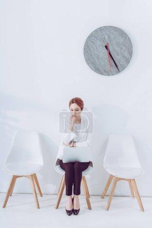 Photo pour Employé pensive assis sur la chaise avec l'ordinateur portatif et l'entrevue d'emploi d'attente - image libre de droit