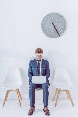Photo pour Bel homme dans les verres assis sur la chaise et en utilisant l'ordinateur portable près de l'horloge - image libre de droit