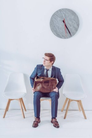 Photo for Worried man in glasses holding briefcase while waiting job interview - Royalty Free Image