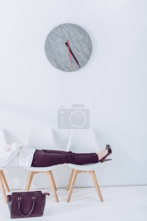 Photo for Cropped view of woman lying on chairs while waiting job interview - Royalty Free Image
