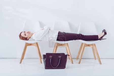 Photo for Attractive employee lying on chairs near bag while waiting job interview - Royalty Free Image
