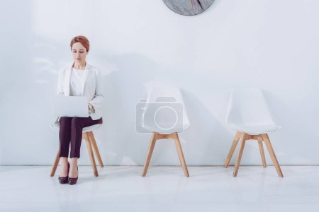 Photo for Beautiful employee using laptop and sitting on chair - Royalty Free Image