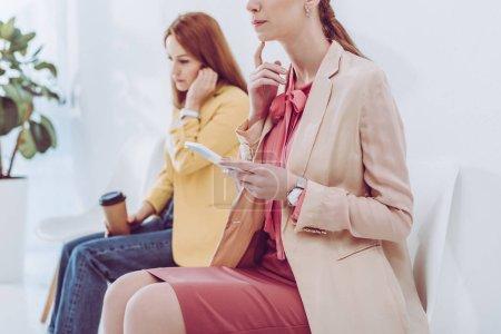 Photo pour Vue recadrée de femme coûteuse en utilisant smartphone près de l'employé avec tasse en papier - image libre de droit