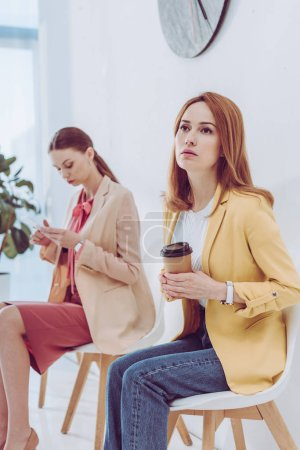 Photo for Selective focus of thoughtful employee with paper cup near woman using smartphone - Royalty Free Image