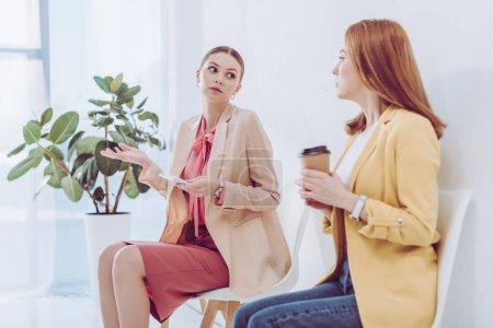 Photo pour Focus sélectif de femme attirante tenant Smartphone et gestes près employé avec tasse en papier - image libre de droit