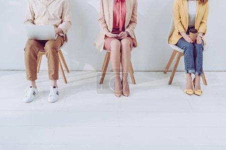 Photo pour Vue recadrée de l'employé assis avec la tasse de papier près de l'homme et de la femme utilisant des gadgets - image libre de droit