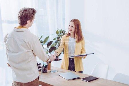 Photo pour Heureux recruteur tenant le presse-papiers et serrant la main avec l'employé dans le bureau moderne - image libre de droit
