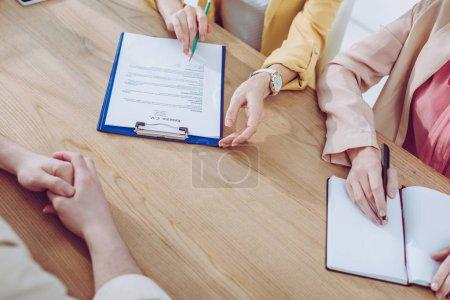 Photo pour Vue recadrée du recruteur tenant le crayon et le presse-papiers près collègue et femme sur l'entrevue d'emploi - image libre de droit