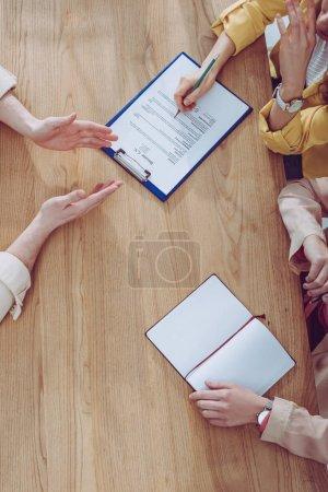 Photo pour Vue de dessus de la femme gestes près recruteur retenant le crayon et collègue sur l'entrevue d'emploi - image libre de droit