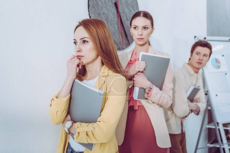 Photo for Selective focus of worried attractive women and man waiting in line with folders - Royalty Free Image