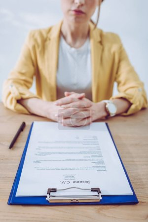 Photo for Selective focus of clipboard with resume cv lettering near recruiter sitting with clenched hands - Royalty Free Image