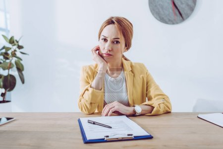 Photo for Sad recruiter in yellow jacket sitting near clipboard and pen - Royalty Free Image